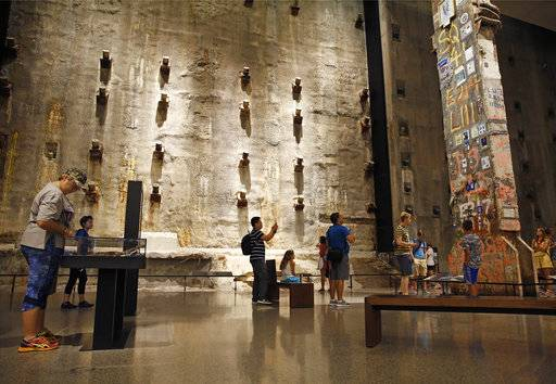 "In this July 11, 2017 photo, visitors to the Foundation Hall at the National September 11 Memorial and Museum view the slurry wall, rear, and a beam from one of the World Trade towers, right, that was preserved by rescue and recovery workers at the site in New York. Last winter the U.S. tourism industry worried about a ""Trump slump,"" fearing that Trump administration policies might discourage international travelers from visiting the U.S. But statistics from the first half of 2017 suggest that the travel to the U.S. is robust and a number of sectors have reported increased international visitation, with one expert calling it a ""Trump bump."" The museum is among those reporting more international visitors this year compared to the same period in 2016. (AP Photo/Kathy Willens)"