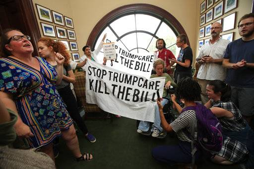 Protesters agains the Republican health care bill gather inside the office of Sen. Rob Portman, R-Ohio, on Capitol Hill in Washington, Monday, July 17, 2017. (AP Photo/Manuel Balce Ceneta)