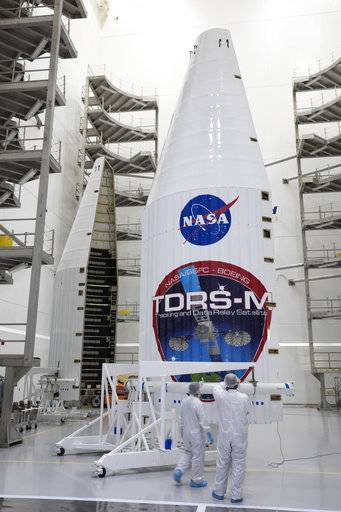 In a July 13, 2017 photo provided by NASA, the payload fairing for NASA's Tracking and Data Relay Satellite, TDRS-M, is inspected prior to encapsulating the spacecraft, inside the Astrotech facility in Titusville, Fla. NASA said Monday, July 17, 2017, that one of the antennas on the Tracking and Data Relay Satellite, was damaged last Friday. The mishap could delay what was supposed to be an Aug. 3 liftoff aboard an Atlas V (five) rocket. (Glenn Benson/NASA via AP)