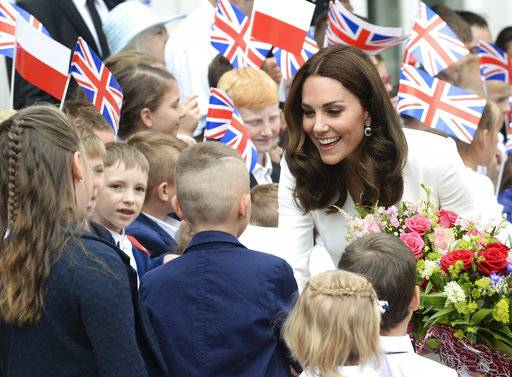 Children welcome Britain's Kate, the Duchess of Cambridge, during her visit with Britain's Prince William, in front of the presidential palace, in Warsaw, Poland, Monday, July 17, 2017. The Duke and Duchess of Cambridge and their children arrived in Poland on Monday, on the first leg of a goodwill trip to two European Union nations that seeks to underscore Britain's friendly ties despite its negotiations to leave the bloc. (AP Photo/Alik Keplicz)