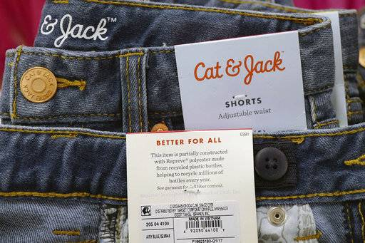 In this Friday, July 14, 2017, photo, Cat & Jack jeans are on display at a Target store, in New York. The jeans are made with Repreve polyester fabric, created from recycled plastic bottles. For this year's back-to-school shopping season, green is the new black. Increasingly, parents and their kids are looking for second-hand clothing or fashions made from reused material.