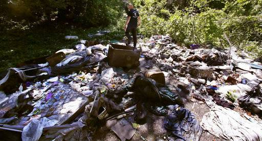 In this Wednesday June 7, 2017 photo, activist Rocky Morrison walks through an encampment where opioid addicts shoot up along the Merrimack River in Lowell, Mass. Morrison leads a cleanup effort along the Merrimack River, which winds through the old milling city of Lowell, and has recovered hundreds of needles in abandoned homeless camps that dot the banks, as well as in piles of debris that collect in floating booms he recently started setting.