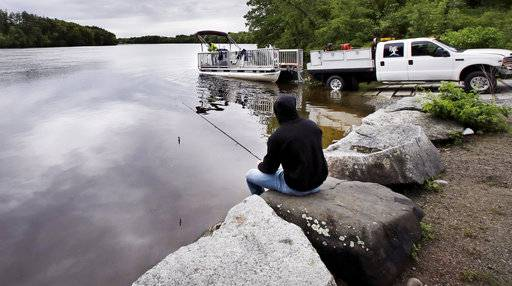 "In this Wednesday June 7, 2017 photo, Kevin Garcia fishes along the banks of the Merrimack River as a ""Clean River Project"" recovery boat is offloaded in Chelmsford, Mass. Syringes left by drug users amid the heroin crisis are turning up everywhere. They hide in weeds along hiking trails and in playground grass, get washed into rivers and onto beaches, and lie scattered about in baseball dugouts and on sidewalks and streets. There are reports of children finding them and getting poked."
