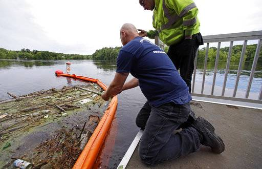 "In this Wednesday June 7, 2017 photo activist Rocky Morrison, left, of the ""Clean River Project"" examines a boom filled with waste collected from a recovery boat on the Merrimack River in Chelmsford, Mass. Morrison leads a cleanup effort along the Merrimack River, which winds through the old milling city of Lowell, and has recovered hundreds of needles in abandoned homeless camps that dot the banks, as well as in piles of debris that collect in floating booms he recently started setting."
