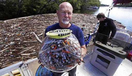 "In this Wednesday June 7, 2017 photo, activist Rocky Morrison, of the ""Clean River Project"", holds up a fish bowl filled with hypodermic needles, that were recovered during 2016, on the Merrimack River next to their facility in Methuen, Mass. Morrison leads a cleanup effort along the Merrimack River, which winds through the old milling city of Lowell, and has recovered hundreds of needles in abandoned homeless camps that dot the banks, as well as in piles of debris that collect in floating booms he recently started setting."