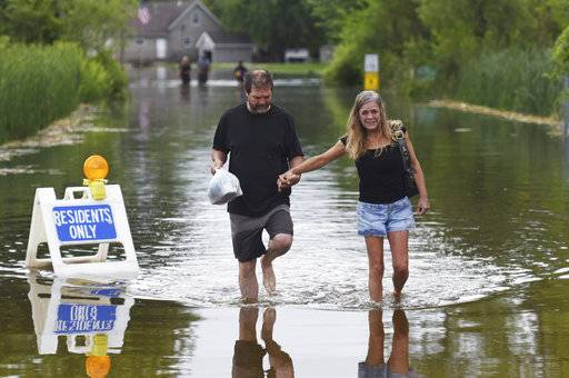 Dan Robinson and April Cissell walk through the flooded Knollwood Road in Ingleside, Ill. on Sunday, July 16, 2017. Knollwood Park subdivision residents have been parking along Route 59 and taking a boat or wading through the water to get to their homes. (Paul Valade/Daily Herald via AP)