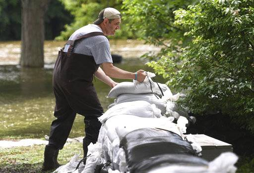 Algonquin resident Dan Prokop piles sandbags along the Fox River behind his La Fox River Drive home Sunday, July 16. 2017 in Fox Lake, Ill. Prokop starting the sandbagging process Thursday and makes adjustments as the river rises around his Illinois home. (Paul Valade/Daily Herald via AP)