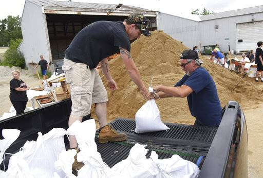 Volunteer Cory Wedge of Round Lake, left, helps Fox Lake resident Dan Vezensky load his truck with sandbags Sunday, July 16, 2017 at the Fox Lake Public Works facility in Fox Lake, Ill. (Paul Valade/Daily Herald via AP)