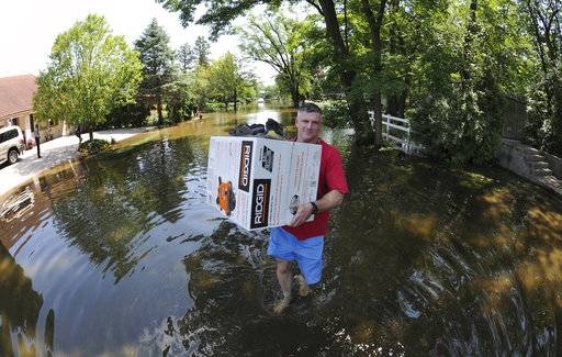 Bill Wilson carries a wet vacuum, with his shoes on top of the box, to his truck as he helps a friend face the reality of the flood on Big Bend Drive in Des Plaines, Ill. Saturday, July 15, 2017. (Mark Welsh/Daily Herald via AP)