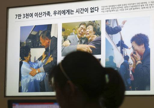 "Pictures showing some reunions of family members from North and South Korea are displayed at the headquarters of the Korea Red Cross in Seoul, South Korea, Monday, July 17, 2017. South Korea offered Monday to talk with North Korea to ease animosities along their tense border and resume reunions of families separated by their war in the 1950s. The signs read "" 73,000 separated families, We do not have time."""