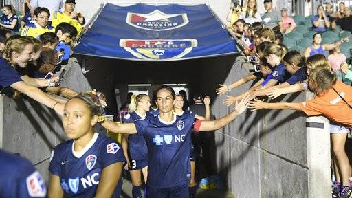 Abby Erceg, center, of the North Carolina Courage, greets fans as the team enters the field before a soccer match against the Seattle Reign, in Cary, N.C., Saturday, July 8, 2017. With 10 games left in the regular season, the Courage sit atop the league standings with 27 points. (Fabian Radulescu/The News & Observer via AP)