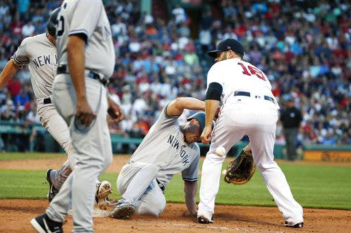 In this Saturday, July 15, 2017 photo, New York Yankees' Matt Holliday, center, retreats to first base and Jacoby Ellsbury arrives on a ground ball as the throw from second base bounces off Ellsbury past Boston Red Sox's Mitch Moreland (18) during the 11th inning of a baseball game in Boston. Red Sox manager John Farrell says Boston will move forward with a formal protest over the lack of an interference call on the play. (AP Photo/Michael Dwyer)