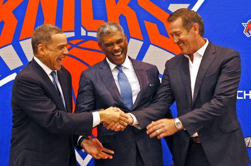 New York Knicks general manager Scott Perry, left, shakes hands with head coach Jeff Hornacek, right, while posing for a picture along with new president Steve Mills, during a news conference in in Greenburgh, N.Y., Monday, July 17, 2017. (AP Photo/Seth Wenig)