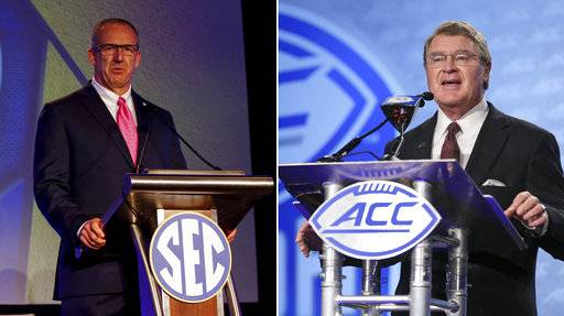 FILE - At left, in a July 10, 2017, file photo, SECÂ conference commissioner Greg Sankey speaks during the NCAA college football Southeastern Conference's annual media gathering in Hoover, Ala. At right, in a July 13, 2017, file photo, ACC Commissioner John Swofford speaks to the media during the Atlantic Coast Conference NCAA college football media day in Charlotte, N.C. The Atlantic Coast Conference has closed the gap on the Southeastern Conference with a four-year run that includes two national championships and two Heisman Trophy winners. Now the ACC and SEC look awfully similar, from their top tiers and divisional imbalances to their Southern-stronghold recruiting bases in overlapping geographic footprints. (AP Photo/File)