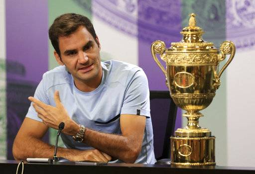 Switzerland's Roger Federer speaks next to the Men's Single's tennis trophy he won on Sunday during a photo call at The All England Lawn Tennis and Croquet Club, Wimbledon, England, Monday July 17, 2017. Federer's eighth Wimbledon title pushed him back up to No.3 in the ATP rankings. (Adam Davy/PA via AP)