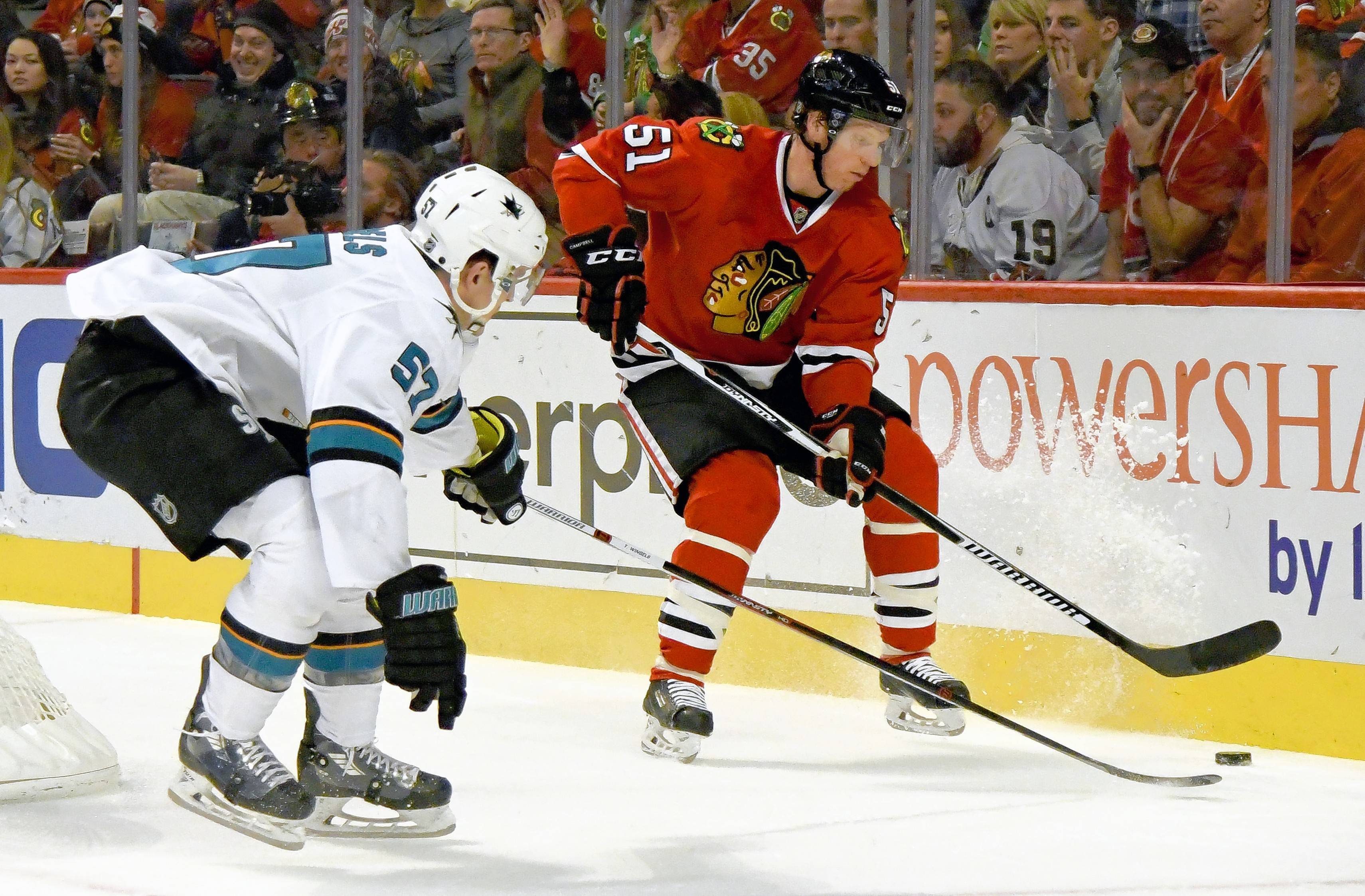 Chicago Blackhawks defenseman Brian Campbell (51) fights for a puck against San Jose Sharks center Tommy Wingels (57) during a game last December in Chicago. Campbell is retiring, and Wingels is now with the Blackhawks after signing as a free agent.