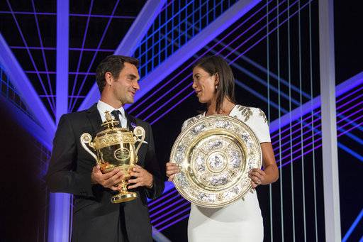 The 2017 Wimbledon singles champions Roger Federer of Switzerland and Garbine Muguruza of Spain pose with their trophies at the Champions Dinner at The Guildhall in London, early Monday July 17, 2017. (Thomas Lovelock/AELTC, Pool via AP)