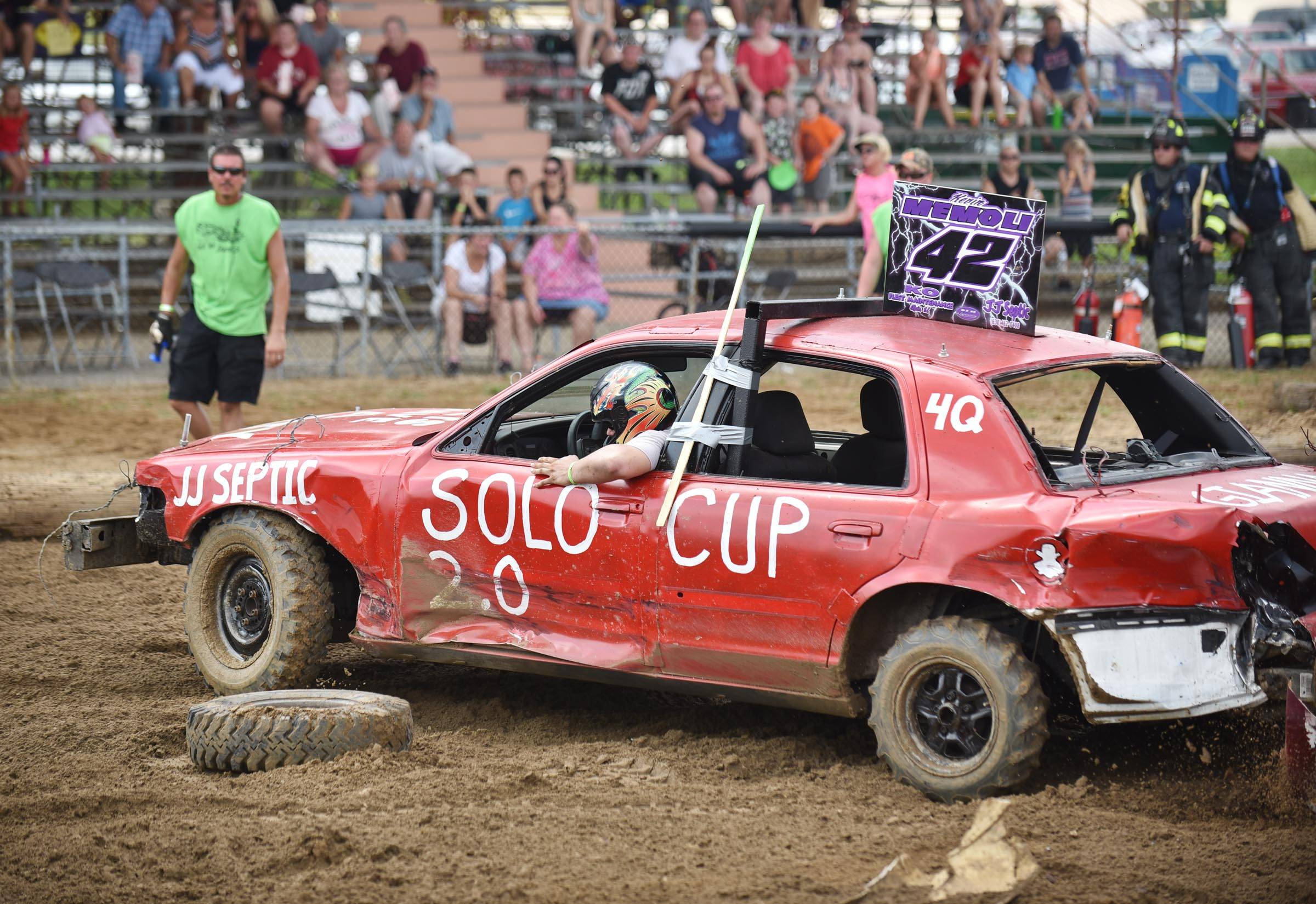 David Memoli, of Geneva looks at a wheel from the car of Brad Ellingsworth of Bolingbrook at the Kane County Fair demolition derby last year. Memoli knocked the wheel off Ellingsworth's car with a powerful hit seconds earlier. Memoli won the heat and advanced to the final.