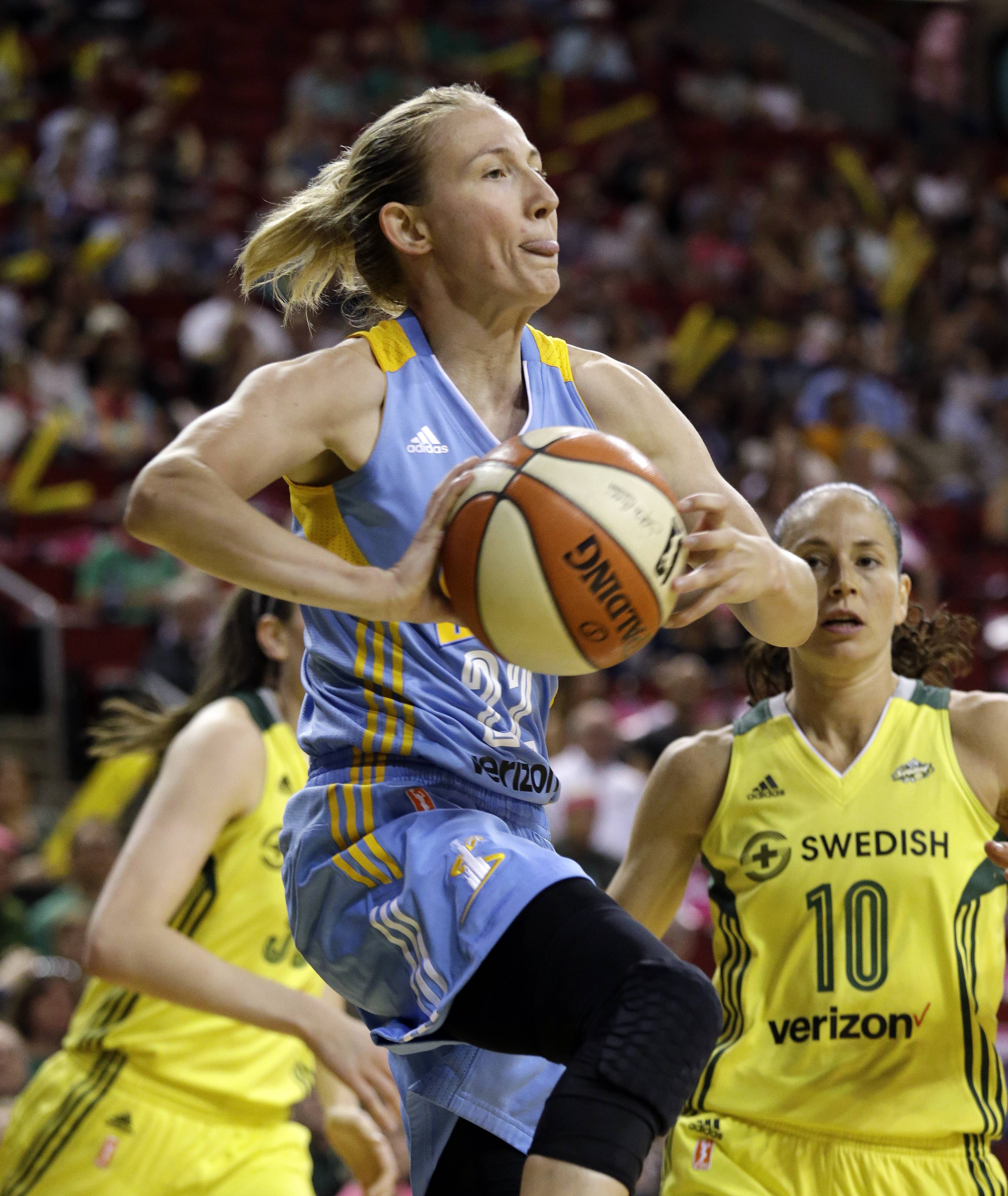 Chicago Sky's Courtney Vandersloot, left, leaps in front of Seattle Storm's Sue Bird to pass under the basket in the first half of a WNBA basketball game Tuesday, July 18, 2017, in Seattle.