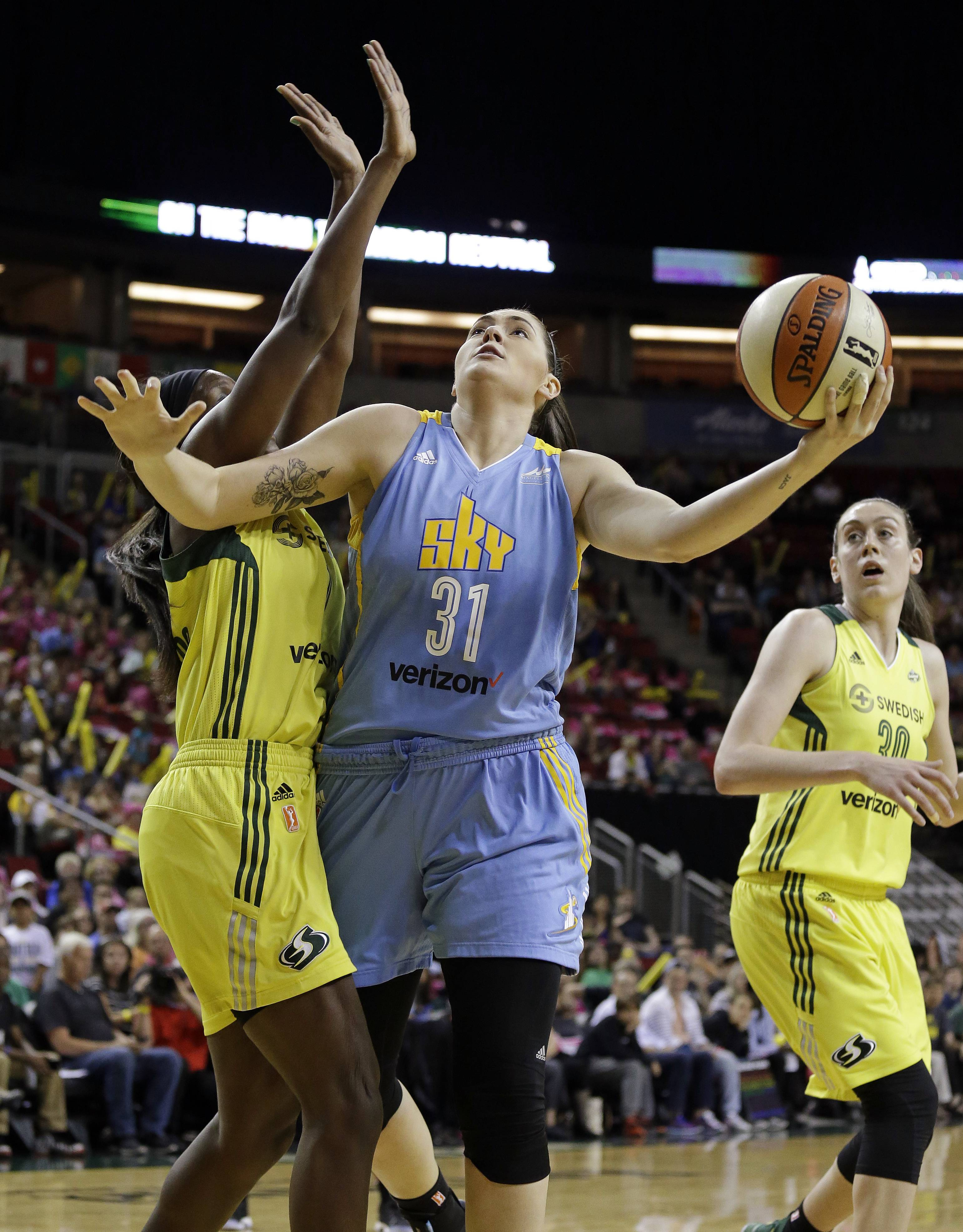 Chicago Sky's Stefanie Dolson (31) gets off a shot between Seattle Storm's Crystal Langhorne, left, and Breanna Stewart during the first half of a WNBA basketball game Tuesday, July 18, 2017, in Seattle.