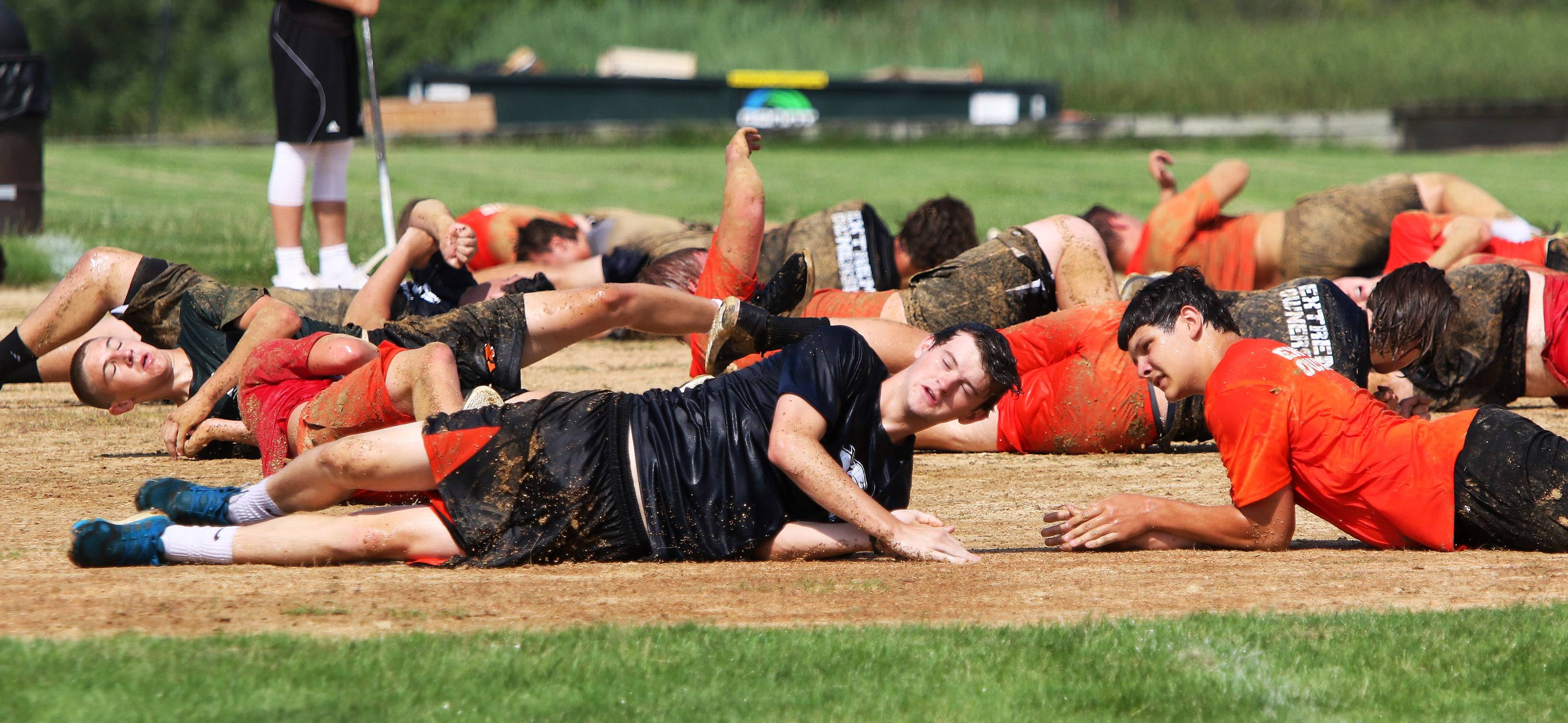 Libertyville High School football players Max Wood, left, John Palmeri and their teammates roll in dirt Wednesday during a training exercise led by two retired Navy SEALs.