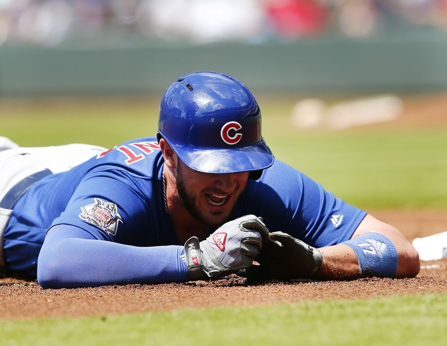 Chicago Cubs third baseman Kris Bryant (17) holds his finger after being injured diving into third base in the first inning of a baseball game against the Atlanta Braves Wednesday, July 19, 2017, in Atlanta.
