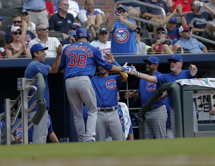 Chicago Cubs pitcher Mike Montgomery (38) is greeted at the dugout by teammates including manager Joe Maddon, right, after hitting a home run in the fifth inning of a baseball game against the Atlanta Braves, Wednesday, July 19, 2017, in Atlanta.