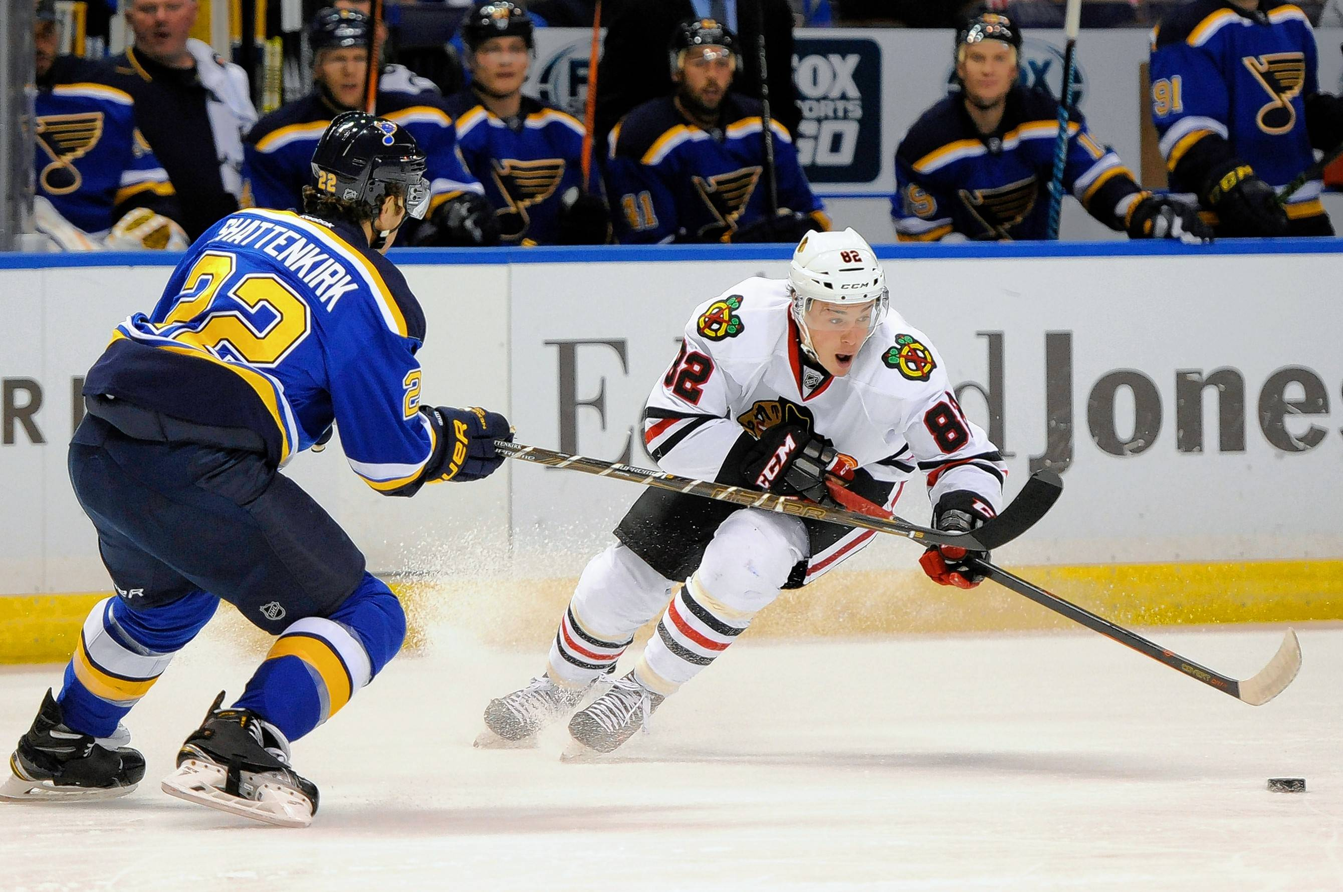 St. Louis Blues' Kevin Shattenkirk (22) and Chicago Blackhawks' Alexandre Fortin (82) reach for the puck during the first period of a preseason NHL hockey game, Oct. 8, 2016, in St. Louis. (AP Photo/Bill Boyce)