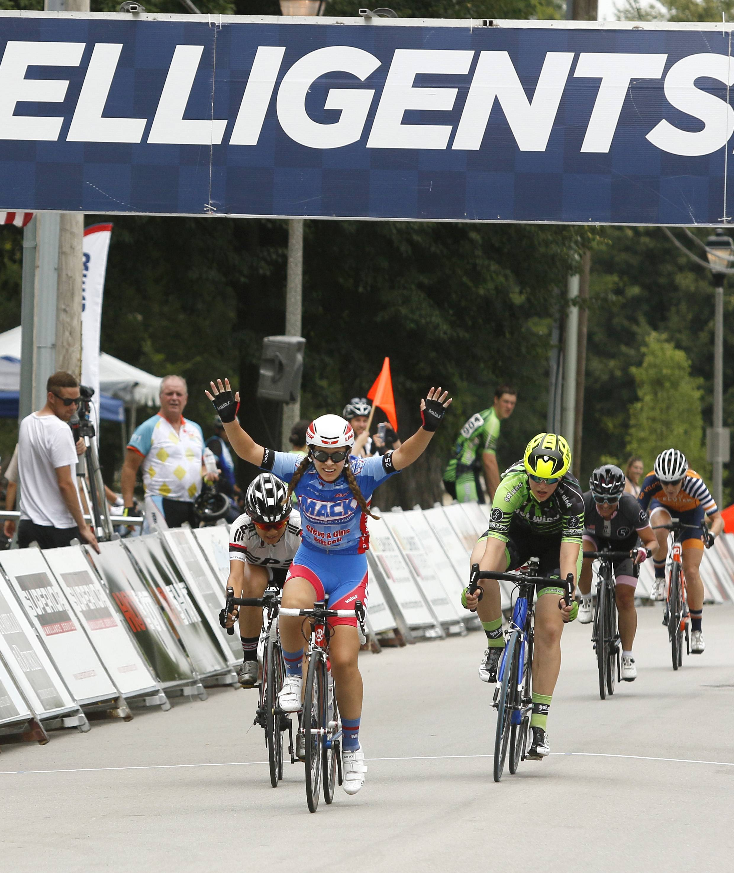 Marissa Carter of St. Charles, Missouri, celebrates after finishing first in one of the women's race categories at the fifth annual Elmhurst Cycling Classic, part of the 10-race Intelligensia Cup. Lydia Chinchilla of Glen Ellyn, right, finished second.