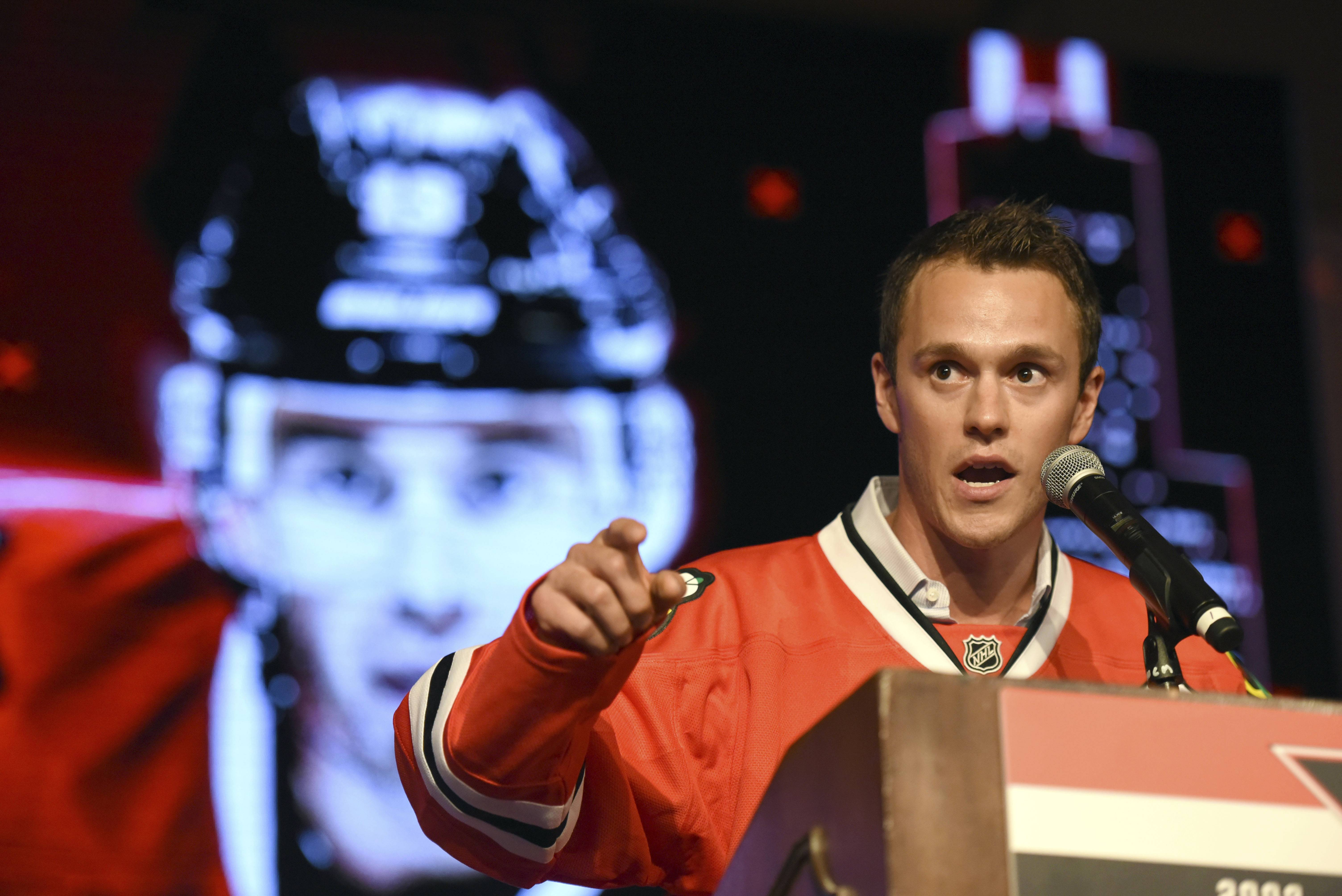 "Blackhawks captain Jonathan Toews speaks to fans during the NHL hockey team's convention Friday night in Chicago. Before the Convention kicked off, Toews said next year's team needs to start thinking as one. No more ""young guys"" and ""veteran guys."" Said Toews: ""We need to get rid of that whole idea and … get everybody together and performing and working the same way."""