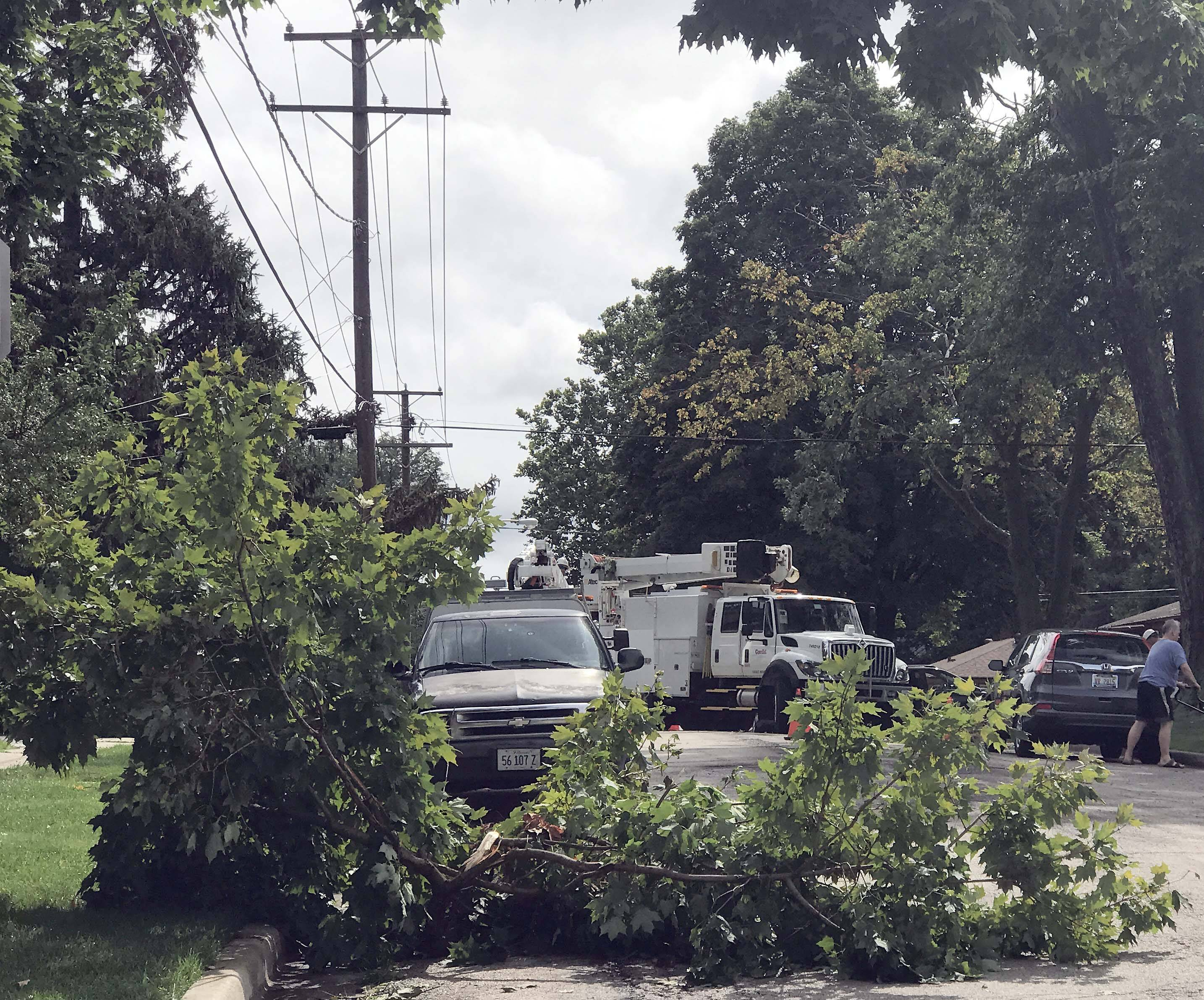 Storm cleanup continues Saturday as ComEd trucks work on Van Street in Elgin. About 5,000 customers in Elgin were out of power Saturday morning, city officials estimated.