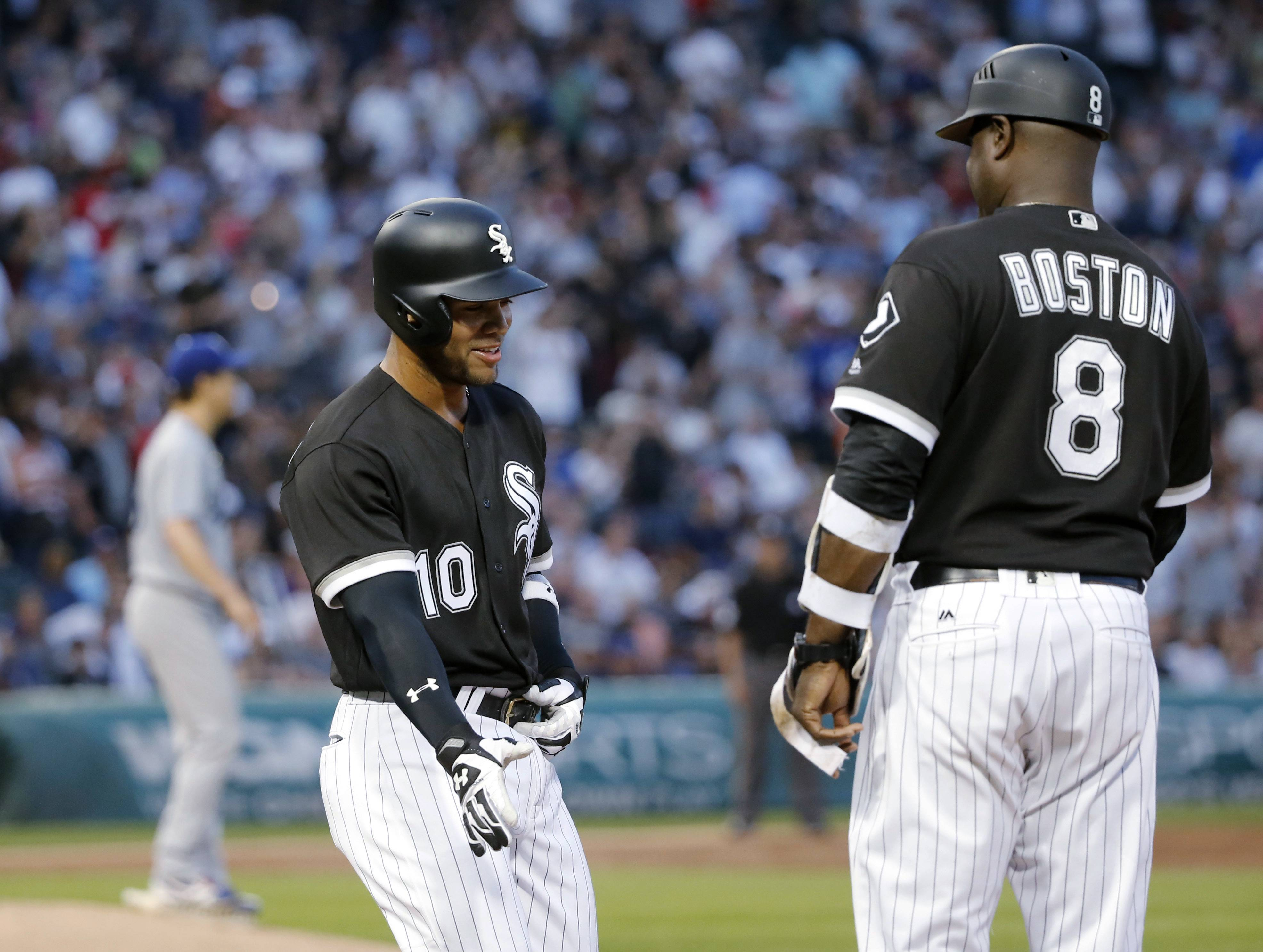 Chicago White Sox's Yoan Moncada smiles at first base coach Daryl Boston after drawing a walk in his first plate appearance on Wednesday. Down 0-2 in the count, Moncada worked for a nine-pitch walk.