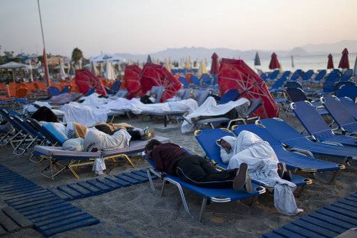 Tourist sleep on sun beds at a beach of the Greek island of Kos, on Saturday, July 22, 2017. Hundreds of residents and tourists on the eastern Greek island of Kos spent the night sleeping outdoors, on beach lounge-chairs, in parks and olive groves or in their cars, a night after a powerful earthquake killed two tourists and injured nearly 500 others across the Aegean Sea region, in Greece and Turkey. (AP Photo/Petros Giannakouris)