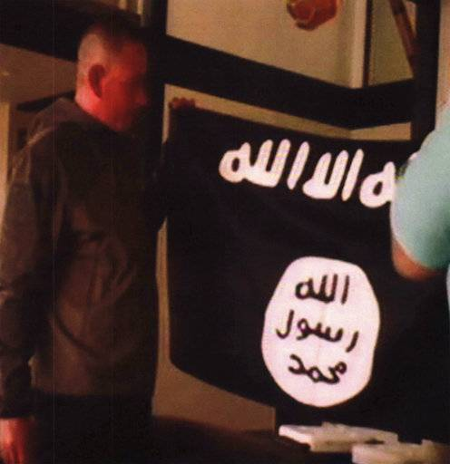 FILE - In this July 8, 2017 file image taken from FBI video and provided by the U.S. Attorney's Office in Hawaii on July 13, 2017, Army Sgt. 1st Class Ikaika Kang holds an Islamic State group flag after allegedly pledging allegiance to the terror group at a house in Honolulu. A federal grand jury in Hawaii has indicted Kang for attempting to provide material support to the Islamic State group. Kang was indicted Friday, July 21 after he was arrested by an FBI SWAT team on July 8. Kang was ordered held without bail. Because of the indictment, Kang will no longer have a preliminary hearing that was scheduled for Monday, July 24. (FBI/U.S Attorney's Office, District of Hawaii via AP, File)