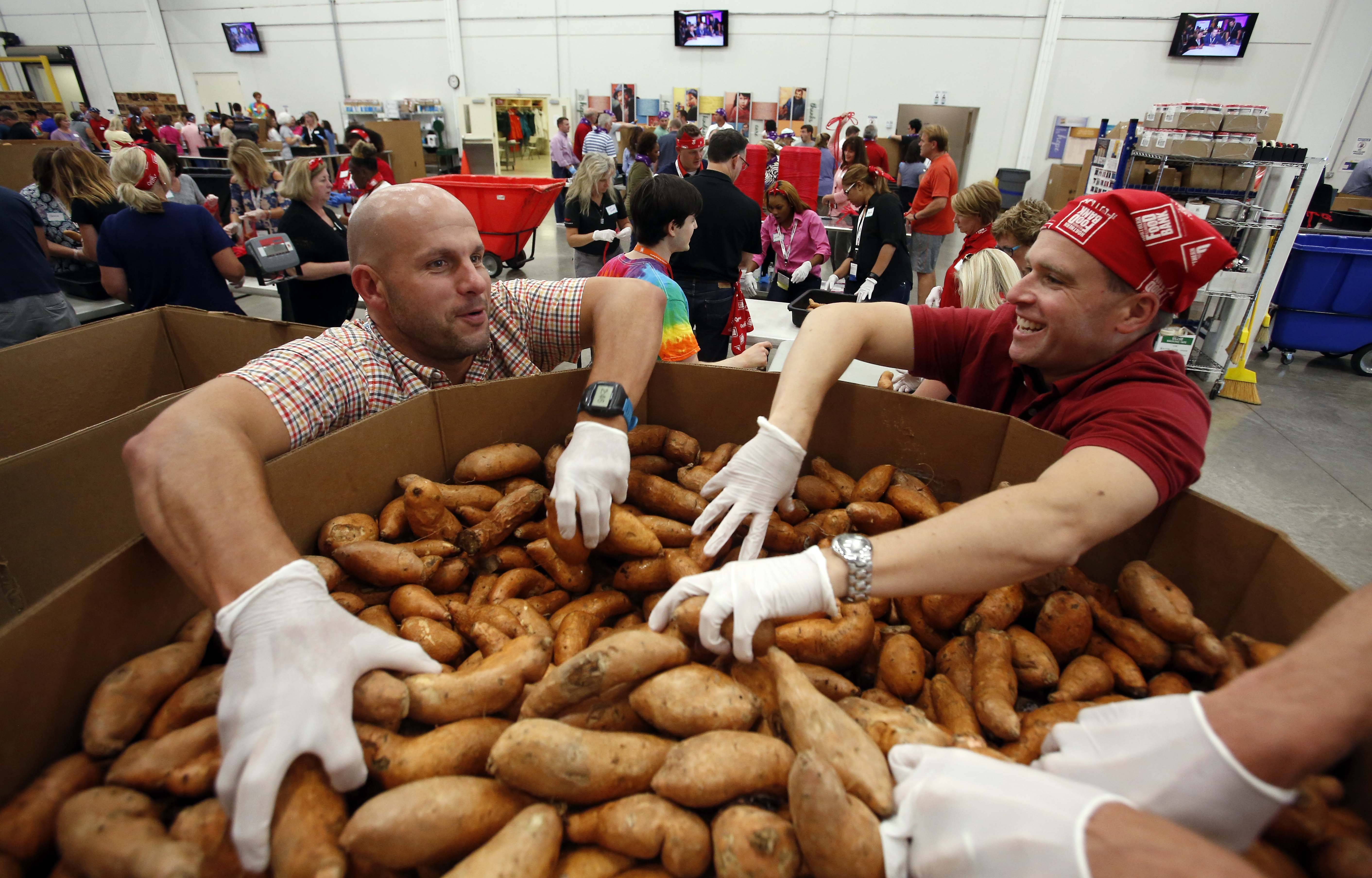 Brad Price, of Knoxville TN, left, and Paul Nicks of Bartlett, and about 250 employees from Kellogg's volunteered to pack food Wednesday afternoon at the Northern Illinois Food Bank in Geneva. It's the largest volunteer group packing event the food bank has ever done.