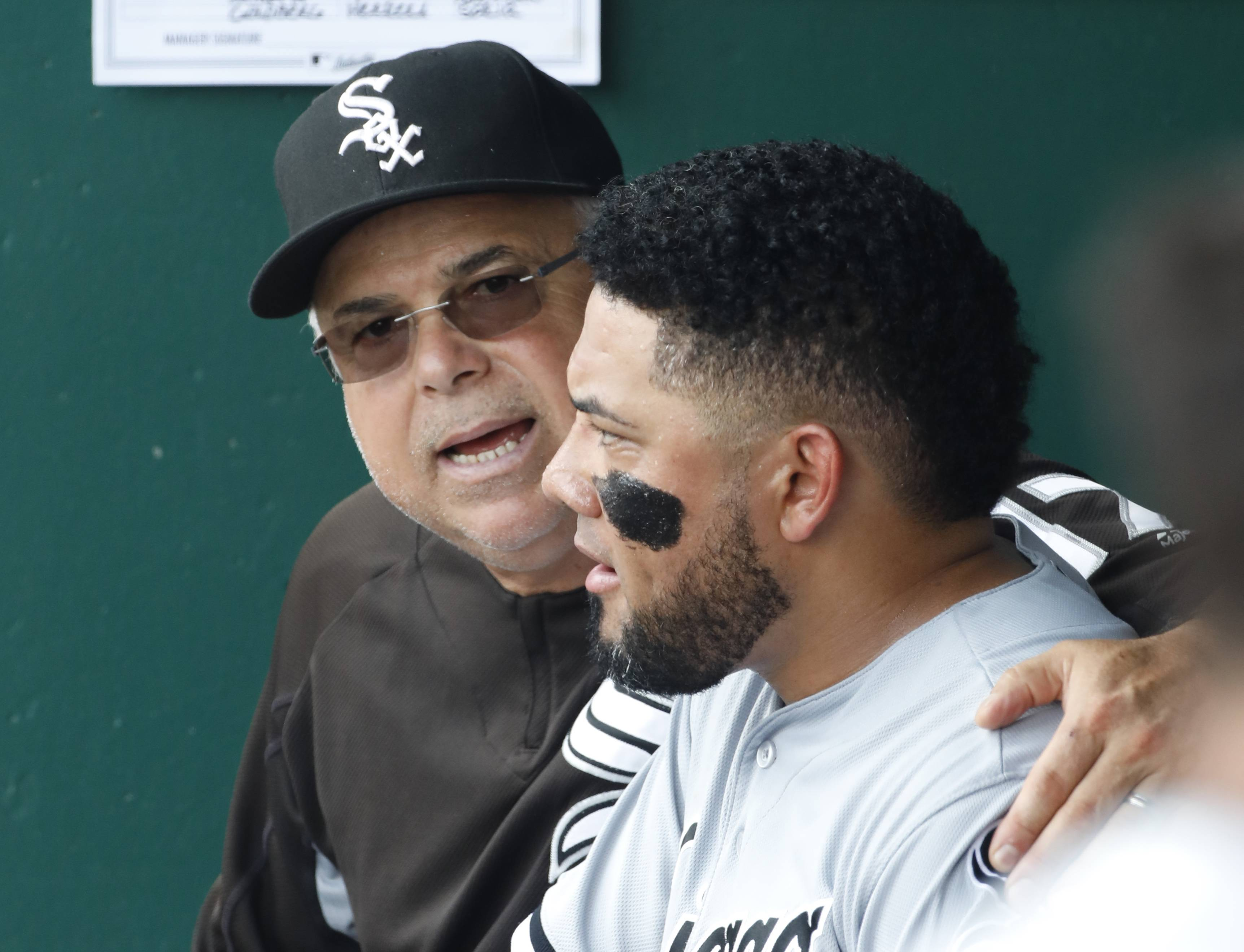 Chicago White Sox manager Rick Renteria, left, talks with Melky Cabrera, right, in the dugout between innings of their team's baseball game against Kansas City Royals at Kauffman Stadium in Kansas City, Mo., Sunday, July 23, 2017.