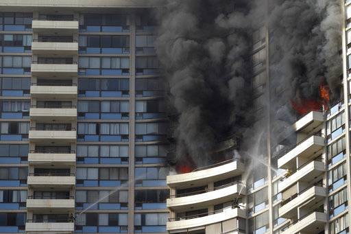 FILE - In this July 14, 2017 file photo, firefighters on several balconies spray water upwards while trying to contain a fire at the Marco Polo apartment complex in Honolulu. Across the United States, there is a mixed bag of laws on whether older high-rise apartment buildings must install fire sprinklers that weren't required when the towers were first built. Many cities _ including New York, Chicago, Dallas and San Francisco _ still have high-rises without the safety measure. Cost is often cited, but after the deadly blaze in Honolulu, many question if the economics outweigh the potential for tragedy. (AP Photo/Marco Garcia, File)