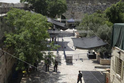 "Israeli border police officers stand guard near newly installed cameras at the entrance to the Al Aqsa Mosque compound in Jerusalem's Old City, Sunday, July 23, 2017. Israel installed new security cameras Sunday at the entrance to a sensitive Jerusalem holy site, as officials began indicating it was considering ""alternatives"" to the metal detectors at the contested shrine that set off a weekend of violence and raised tensions in the region. (AP Photo/Mahmoud Illean)"