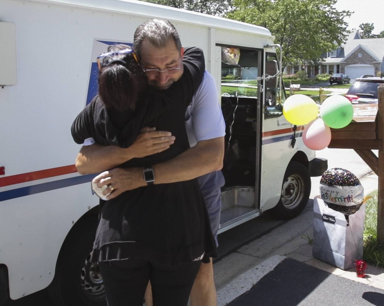 Retiring mailman Tom Nemec gets a hug Monday from Mari Bartilotta in Winfield Estates. Nemec has delivered mail to the neighborhood for nearly 30 years.