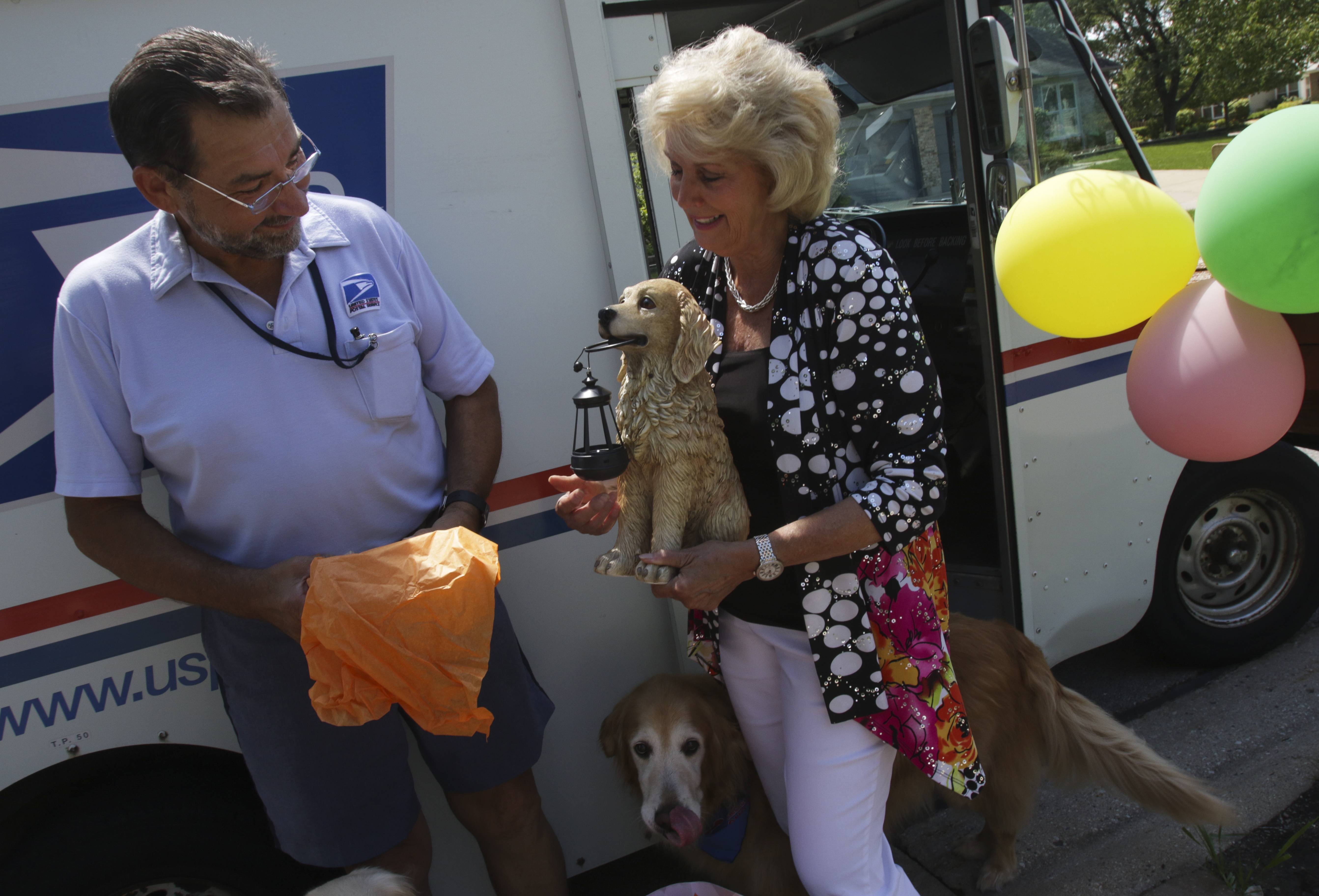 Linda Croft gives Nemec -- a letter carrier much-loved by neighborhood dogs -- a sculpture of a golden retriever.
