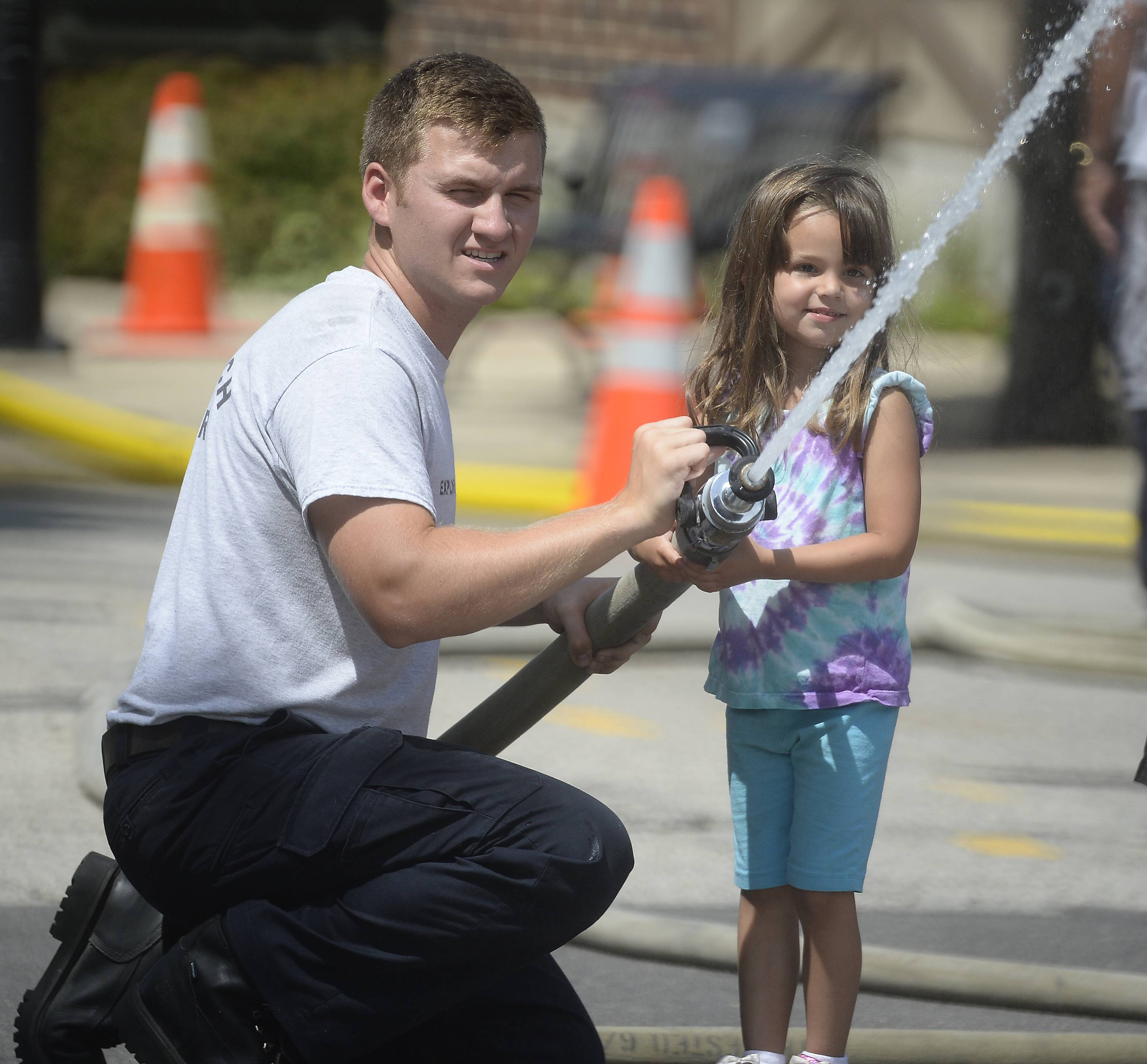 Jack Logan of the Lake Zurich fire department Explorers helps Brooklyn Strauss, 4, of Hawthorn Woods master the fire hose before the water fight battles started at Lake Zurich's Alpine Festival on Saturday.