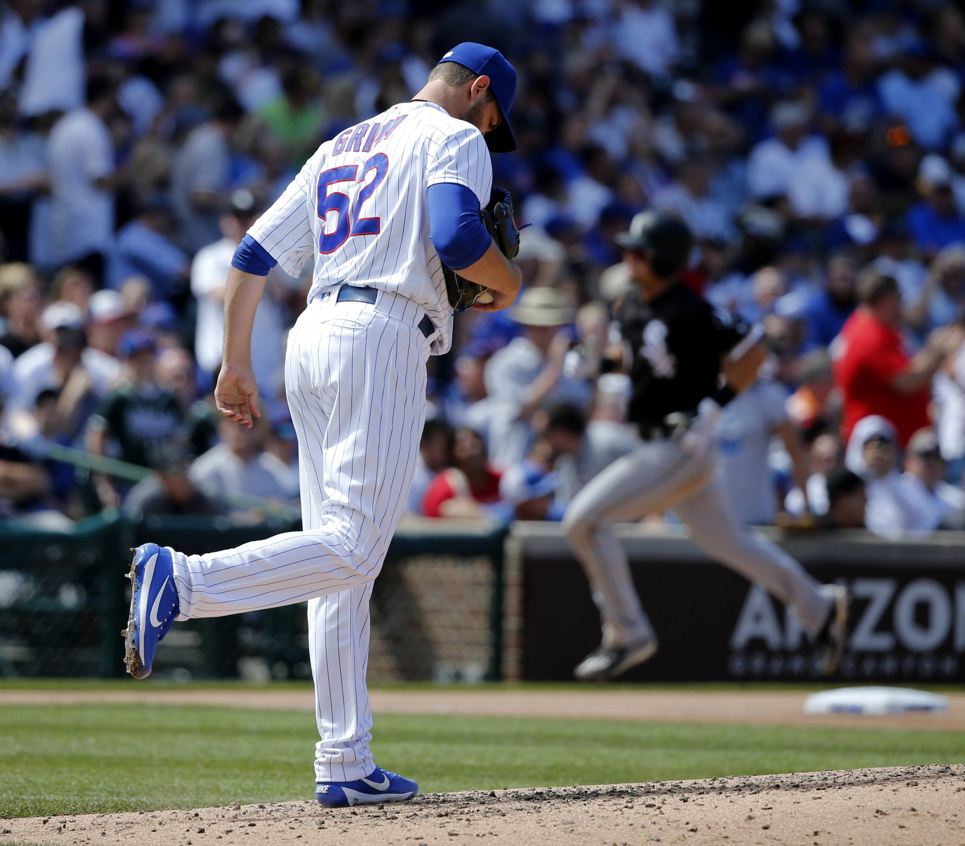 Chicago Cubs relief pitcher Justin Grimm returns to the mound after giving up a home run to Chicago White Sox's Adam Engel, background right, during the sixth inning of a baseball game Monday, July 24, 2017, in Chicago.