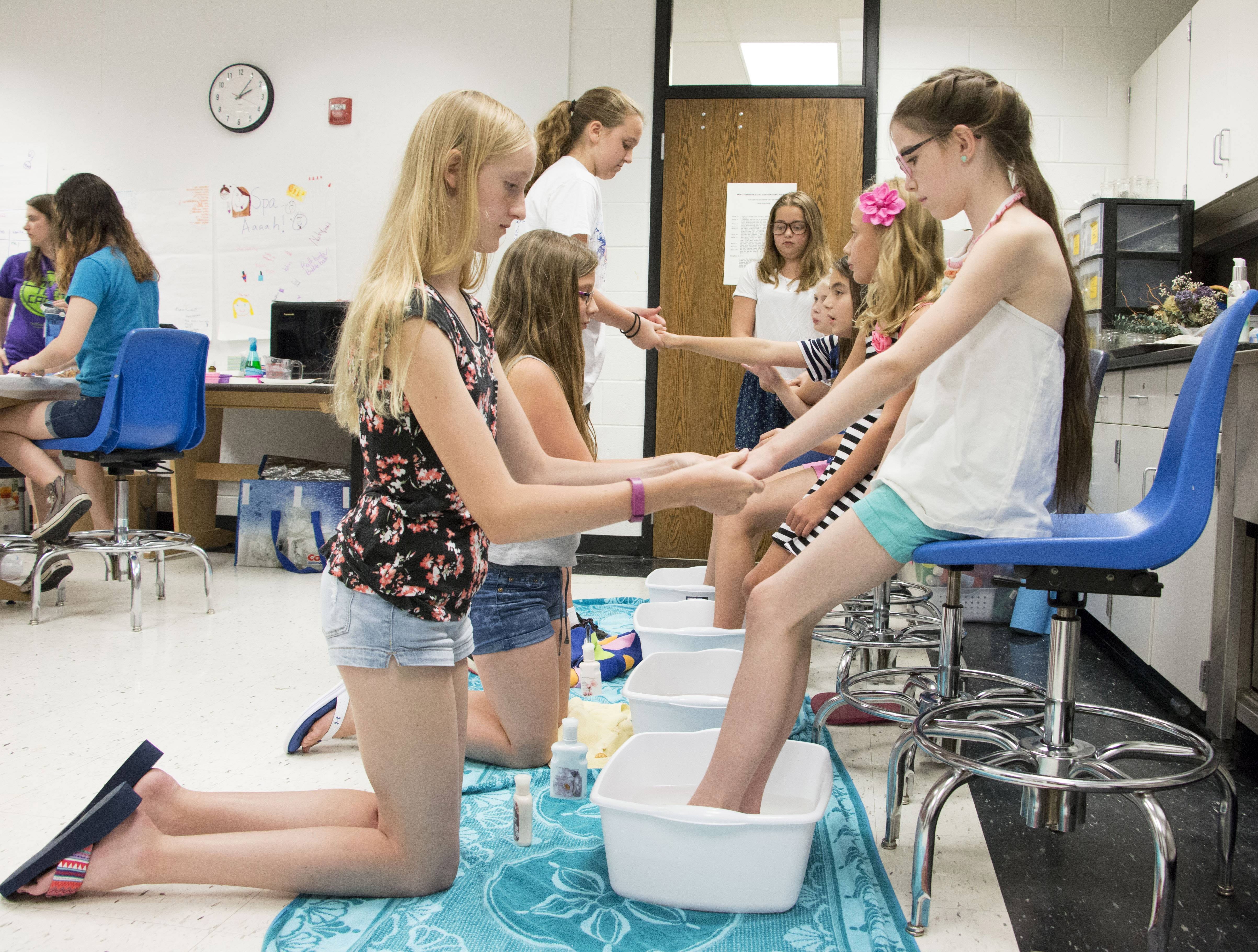 Lauren Courtney, 13, of Lake in the Hills, massages the hand of Miabella Carzoli, 10, of Woodstock, during their Spa Science class as a practice run for the Ultimate Spa Experience the students created for their guests the next day. The class is part of the Kids and College summer program at McHenry County College.