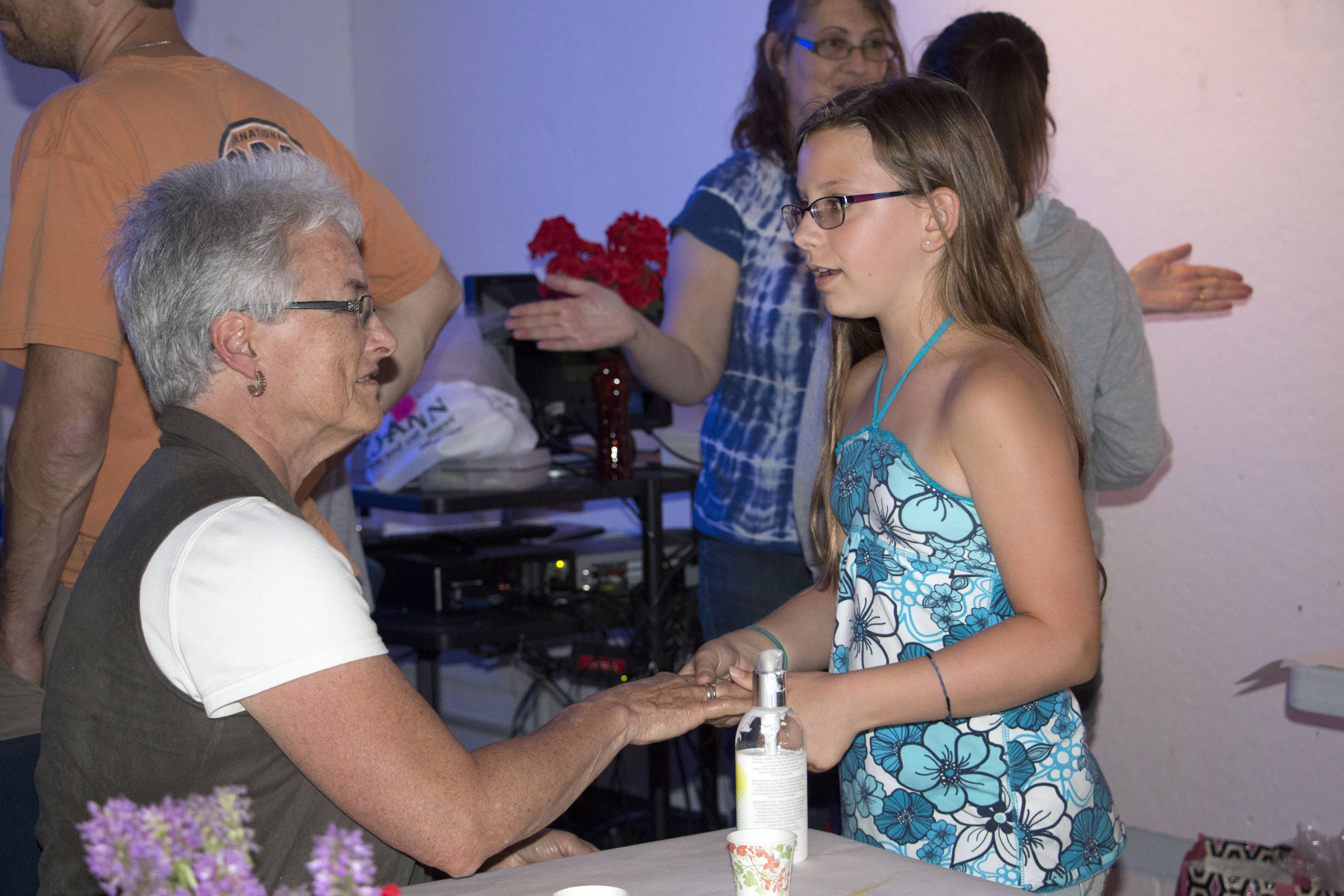 Ella Krotz, 10, of Cary, talks with her grandmother, Candace Sinclair of Cary, as she massages her hand during her Spa Science class where the students created the Ultimate Spa Experience for family members and guests. The class is part of the Kids and College Summer program at McHenry County College.