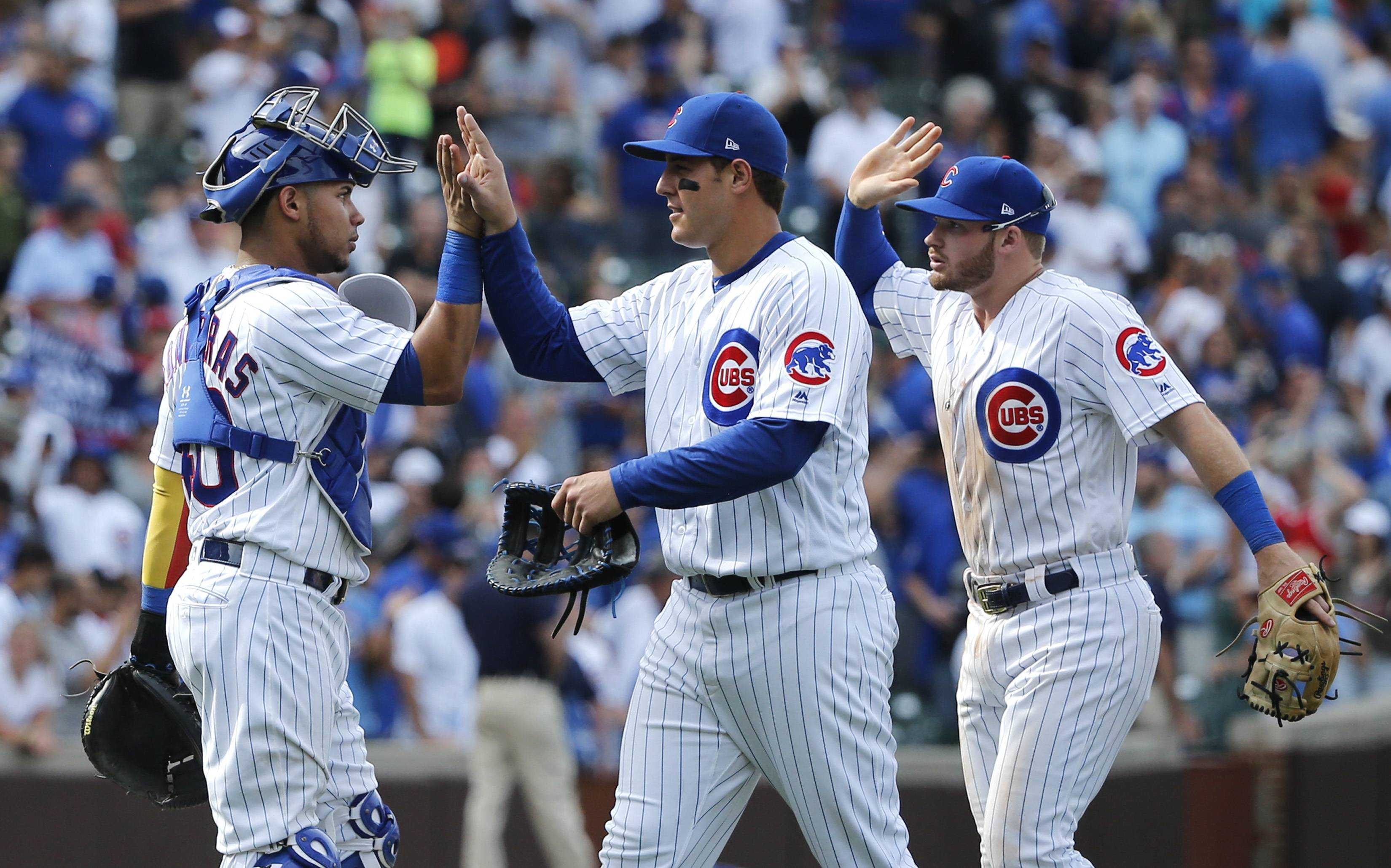 Chicago Cubs' Willson Contreras, left, Anthony Rizzo, center, and Ian Happ celebrate the team's 7-2 win over the Chicago White Sox in a baseball game Tuesday, July 25, 2017, in Chicago.