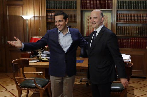 Greek Prime Minister Alexis Tsipras, left, welcomes European Commissioner for Economy Pierre Moscovici at Maximos Mansion in Athens, Tuesday, July 25, 2017. Greece is poised to tap international bond markets for the first time in three years in a move the government hopes will signal the country is ready to emerge from its bailout era.