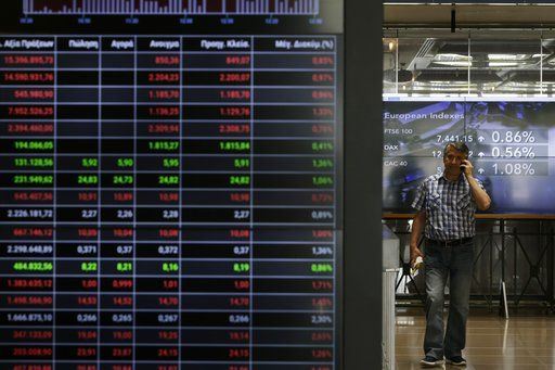 A man speaks his on his cellphone next to an index board at the reception hall of the Stock Exchange in Athens, Tuesday, July 25, 2017. Greece is poised to tap international bond markets for the first time in three years in a move the government hopes will signal the country is ready to emerge from its bailout era.