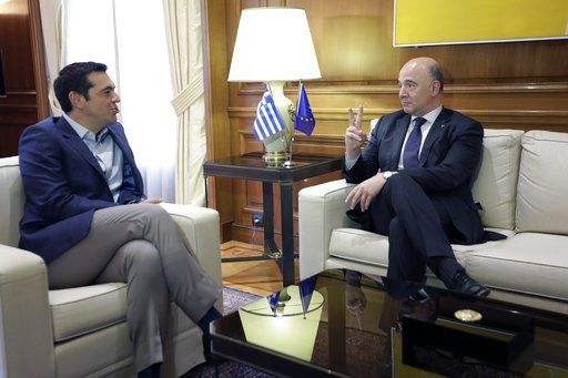 Greek Prime Minister Alexis Tsipras, left, speaks with the European Commissioner for Economy Pierre Moscovici during their meeting at Maximos Mansion in Athens, Tuesday, July 25, 2017. Greece is poised to tap international bond markets for the first time in three years in a move the government hopes will signal the country is ready to emerge from its bailout era.