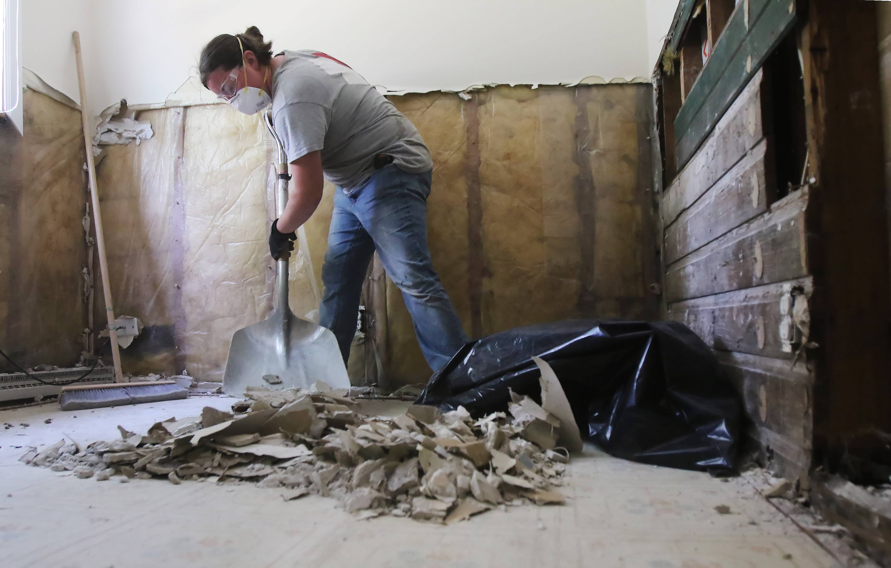 Casey Magoon of Wonder Lake shovels ruined drywall into a trash bag as part of Team Rubicon.