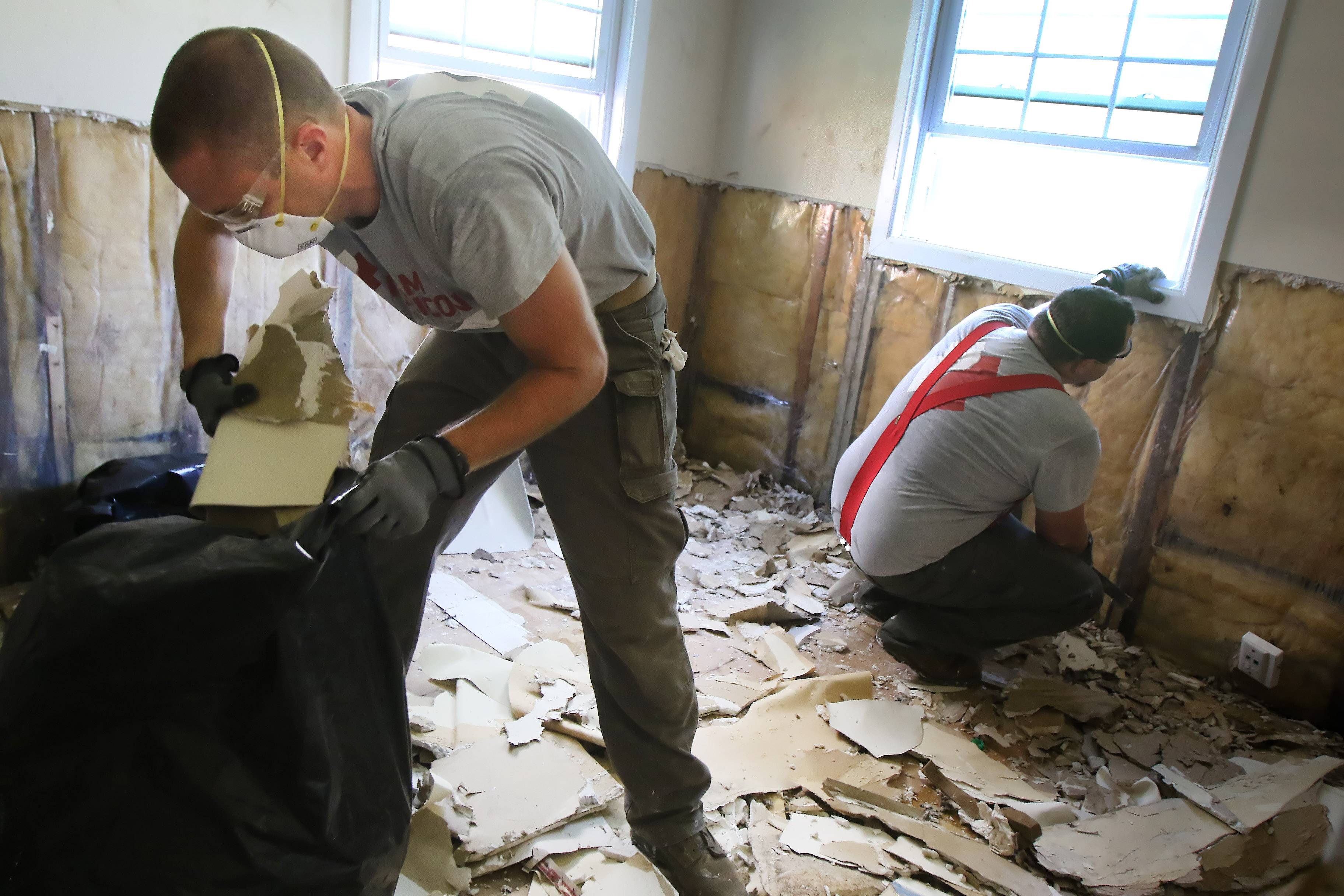 Veterans Adam Martin of Indianapolis, left, and Josh Golson of Portland, Oregon, remove damaged drywall as Team Rubicon repairs a floodeed Round Lake Beach home Tuesday.